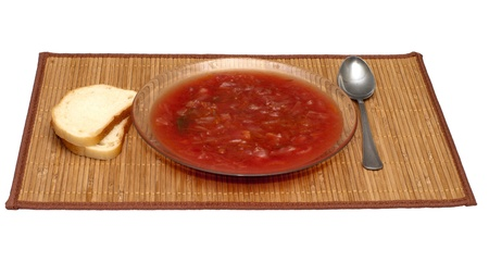 Plate with a borsch and bread on a bamboo mat. photo