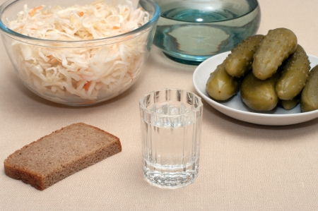 Wine-glass of vodka pickles and sauerkraut close up.