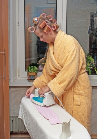hair curlers: Girl with hair curlers in a dressing gown irons clothes.