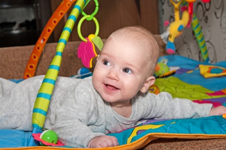 Portrait of the smiling baby creeping on a bed  Stock Photo