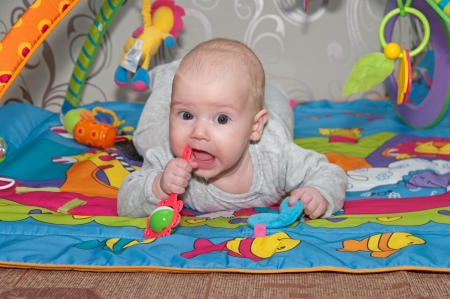 Portrait of the smiling baby with rattle  Imagens