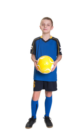 Smiling boy with a soccer ball isolated on a white background.