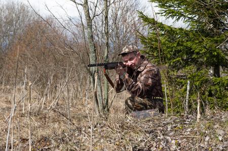 Outdoor shot of man aiming a shotgun.
