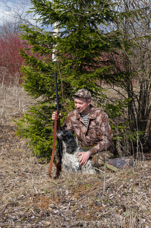 Outdoor shot of man with gun and Russian hunting Spaniel. Stok Fotoğraf