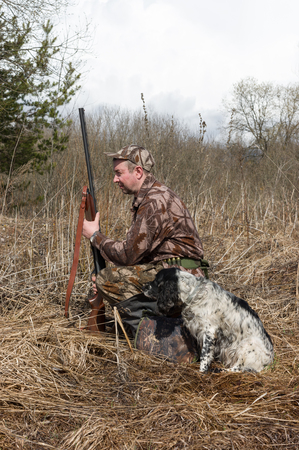 Outdoor shot of man with a gun and Russian hunting Spaniel. Stok Fotoğraf