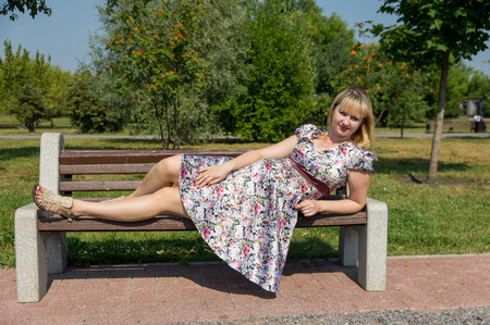 Pregnant woman lies on a wooden bench in the Park Stock Photo