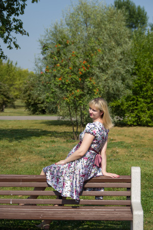 Pregnant woman sitting on wooden bench in park Stock Photo