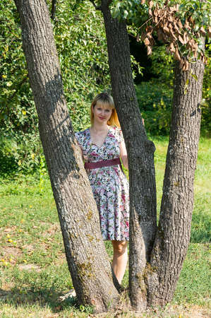 Pregnant woman stands between the trees in Park Sunny summer day.