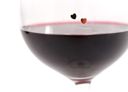 two hearts: Two hearts on a glass with red wine on white background