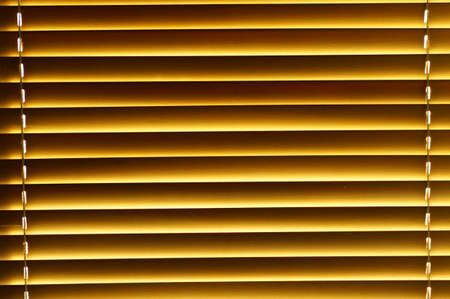 Abstract background - wooden blinds on the window, large brown-golden horizontal stripes lit by the sun Banco de Imagens