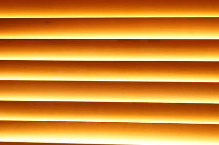 Abstract background - wooden blinds on the window, large brown-golden horizontal stripes lit by the sun