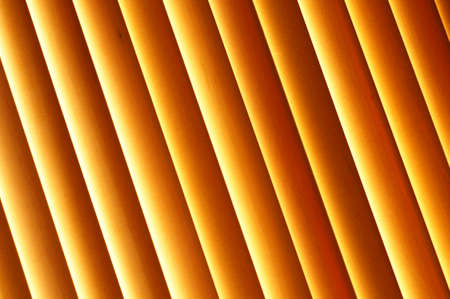 Abstract background - wooden blinds on the window, large brown and gold horizontal stripes lit by the sun