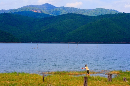 Man Fishing in a lake at Thailand photo