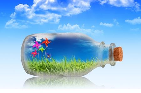 Toy turbina eólica en una botella con la hierba y el cielo