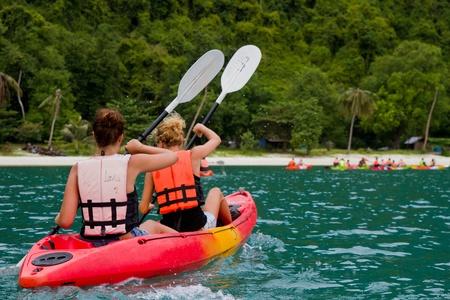 traveler kayaking in the thai ocean from backward view