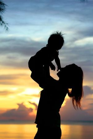 breastfeed: La madre y del beb� en la silueta de la puesta del sol Foto de archivo