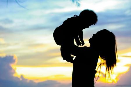 日没時間に母 & 赤ちゃんシルエット 写真素材