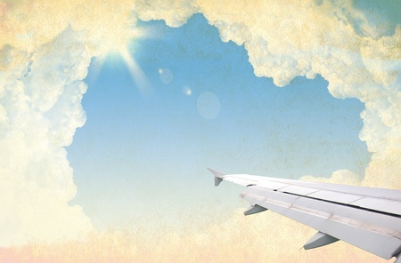 airplane wing, sky and clouds on craft paper photo