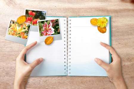 Hands holding note book with photo frame on wood background photo