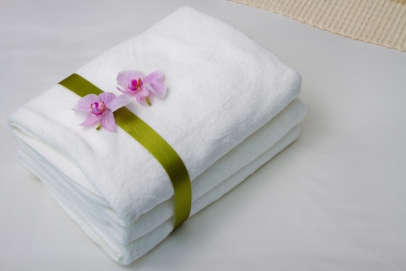 Towels with orchid flower on the bed photo