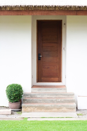 Wooden entrance door in front of residential house photo
