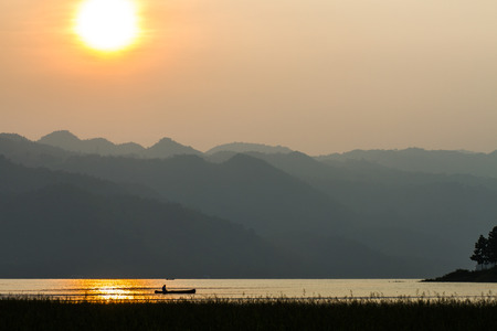 A pair of anglers enjoy a beautiful, golden, misty morning fishing on a lake. photo