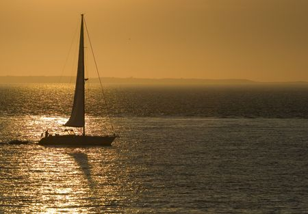 This is a sail boat sailing through a golden reflection photo