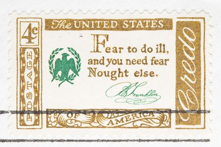 else: This is Vintage 1956 canceled US stamp Credo Fear to do ill and you need fear nought else Stock Photo