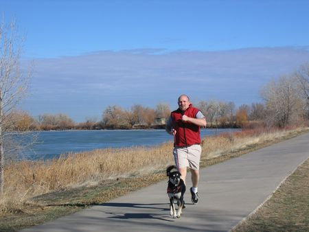 This is a Man running with Dog next to lake