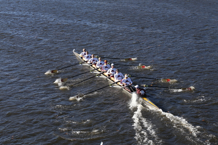 BOSTON - OCTOBER 22, 2016: University of Minnesota races in the Head of Charles Regatta Mens College Eights.  Micheal Schmidt has put his hand in the water to make a tighter turn