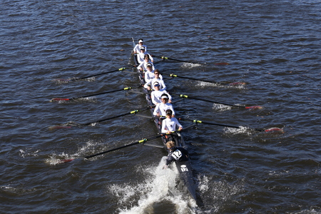 BOSTON - OCTOBER 23, 2016: Winter Park Crew coxswain Sean Kerns puts hand in water in order to turn quickly in the Head of Charles Regatta Mens Youth Eights [PUBLIC RACE]