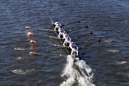 eights: BOSTON - OCTOBER 23, 2016: Winter Park Crew coxswain Sean Kerns puts hand in water in order to turn quickly in the Head of Charles Regatta Mens Youth Eights [PUBLIC RACE]
