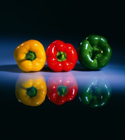 Three fresh colored pepers on a glass table