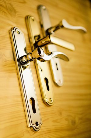 key holes: A series of golden handls on a wooden board 2