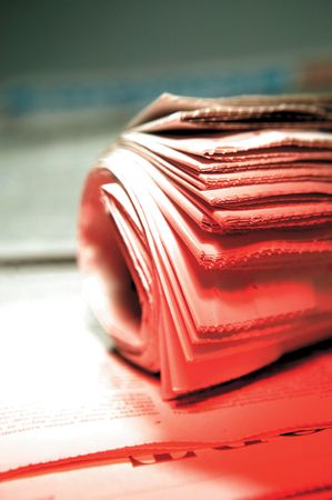 Rolled stack of newspaper under bright red light Stock Photo - 6280765
