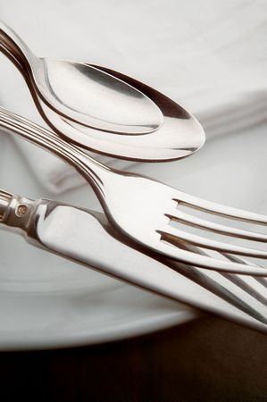 Spoons, fork, knife on a plate with napkin in the background photo
