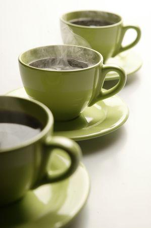 Three steaming mugs in a row in green colors photo