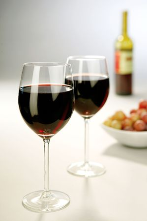 Two full wine glasses with a bottle and grapes in the backgroud photo