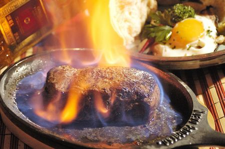 beef steak flambed by the table photo