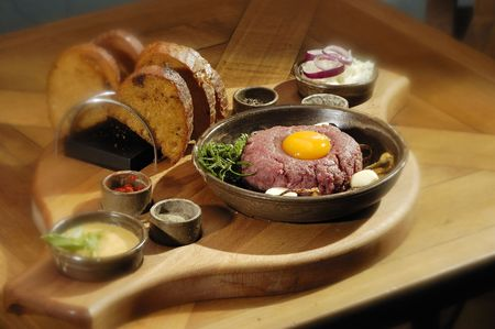 tartar: Steak tartar with the rosemary on the wooden trencher