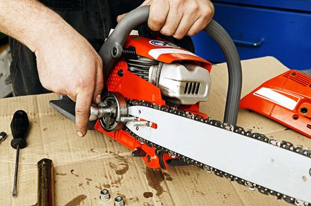 A worker is repairing a chain saw