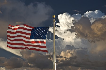 USA flag in the wind dark sky and clouds