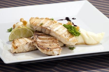 Gegrilde botervis w aardappelpuree doperwten en citroen Stockfoto