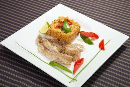 Grilled codfish with red lentil and bell pepper slices photo
