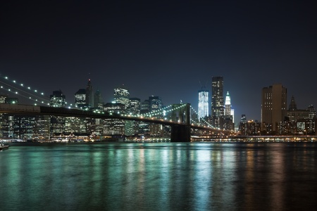 The New York City skyline at night w Brooklyn Bridge photo