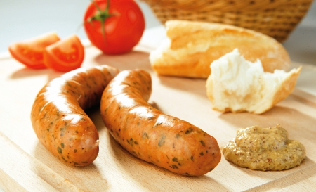 Organic sausages on a wooden board with bread and veggies photo