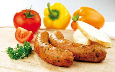 Two sausages, vegetable and bread on a wooden board photo