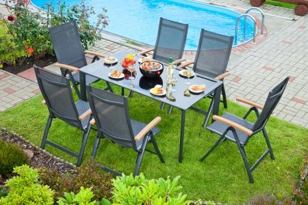 De metalen Tuinmeubelen bij het huis en het zwembad