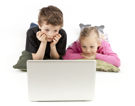kids laptop: Children are lying and watching the silver Notebook Stock Photo