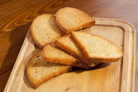 trencher: Crusty toasts on wooden trencher Stock Photo